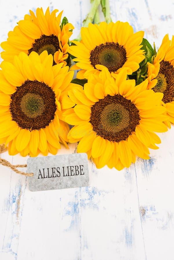 Samla ihop med gula solrosor och kortet med tysk text, Alles Liebe, hjälpmedelgratulationer fotografering för bildbyråer