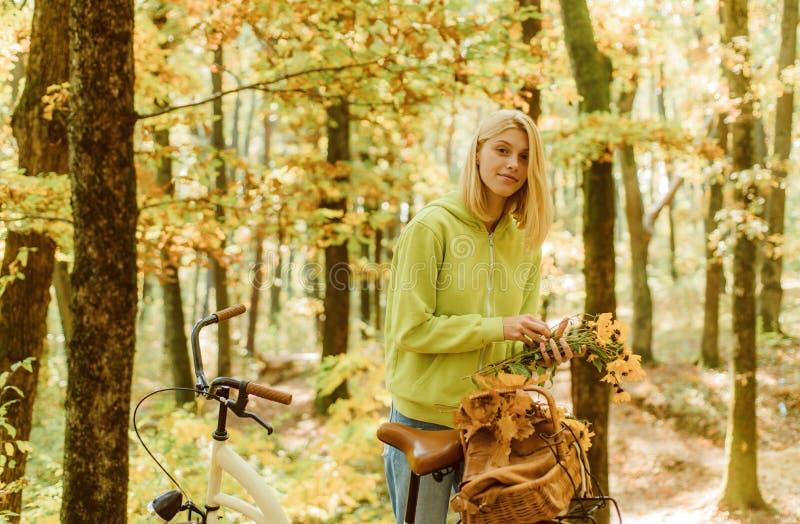 Samla skogblommor Blondinen tycker om för att koppla av skoghöstbuketten Varm h?st Flicka med cykeln och blommor Kvinna royaltyfria foton