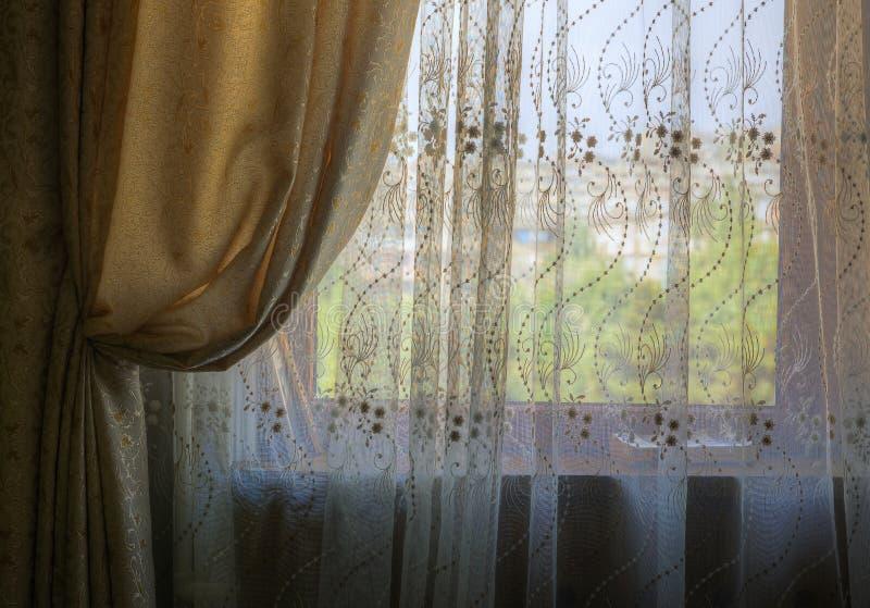 Samlade gardiner och rullgardiner på fönstret av rummet arkivbild