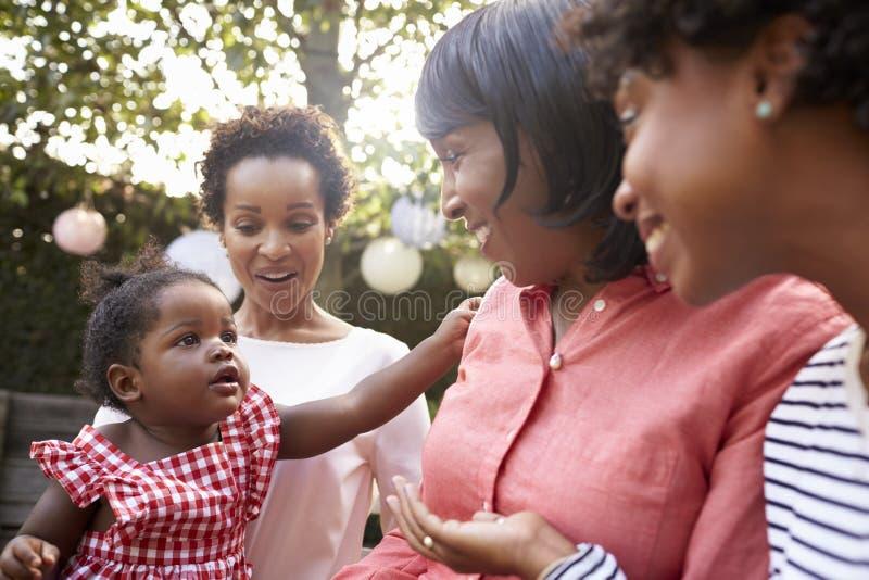 Samlade kvinnliga familjemedlemmar för mång- utveckling i en trädgård royaltyfria foton