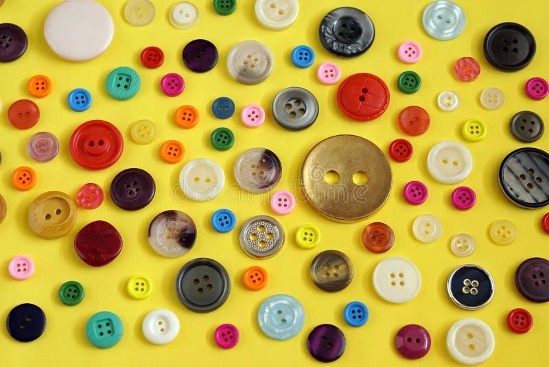 Samling av färgglade sy knappar på gul bakgrund arkivfoton