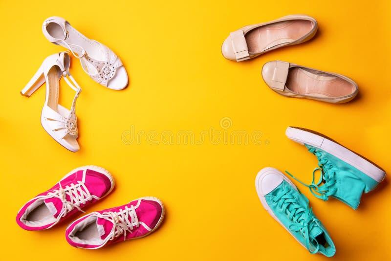 Samling av kvinnors skor p? gul bakgrund royaltyfria foton