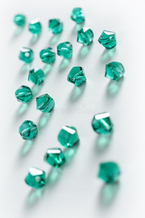 Samling av många gröna dubbla kottekristaller i en vit ask royaltyfri foto