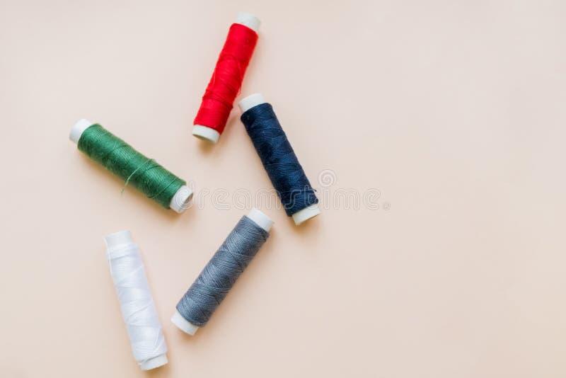 Samling av olika sy trådar på pastellfärgad bakgrund Varje skjutas separat knittinnghjälpmedel naturlig bomull royaltyfri foto