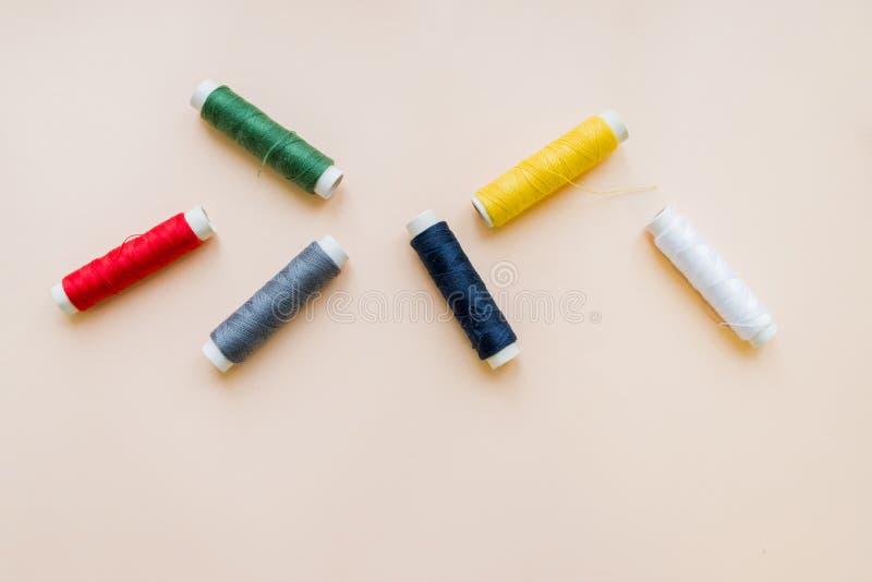 Samling av olika sy trådar på pastellfärgad bakgrund Varje skjutas separat knittinnghjälpmedel naturlig bomull arkivfoton