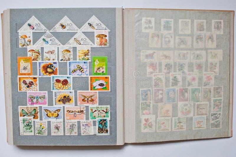 Samling av portostämplar i album från olika länder a royaltyfria bilder