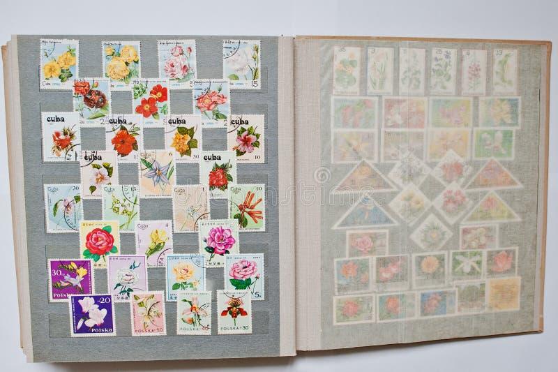 Samling av portostämplar i album från olika länder a royaltyfri foto