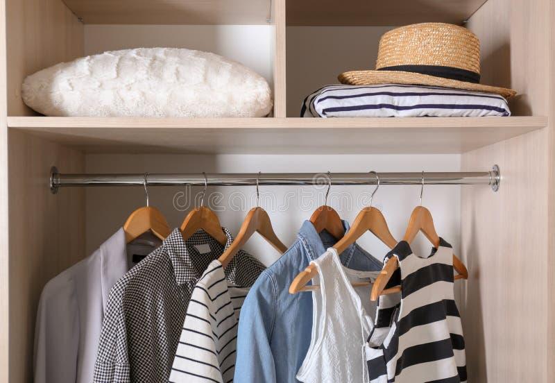 Samling av stilfull kläder och kudden i garderob royaltyfri fotografi