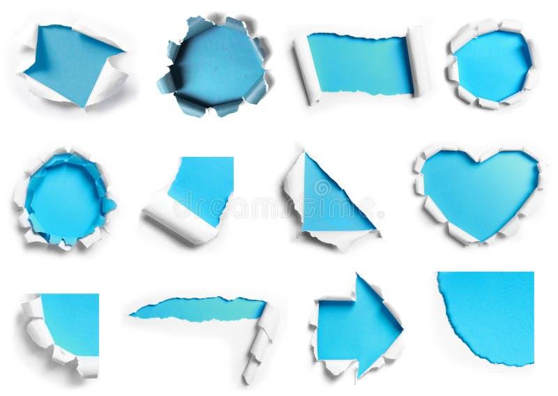 Samling av vitt sönderrivet papper med blå bakgrund i många shap royaltyfri bild
