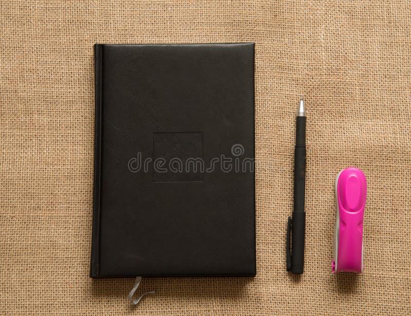 Samling för kontorstillförsel - anteckningsbokhäftapparat på brun säckväv fotografering för bildbyråer