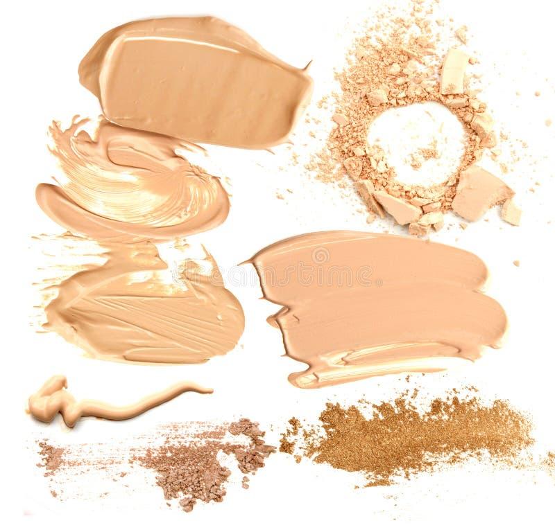 Samlingen av beige fundament och pulver krossade kosmetiska produkter på en vit bakgrund arkivbild