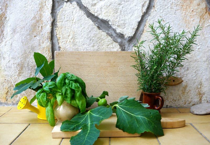 Samlingen av medelhavs- kryddor, rosmarin, basilika, lagersidor och fikonträd på ett lantligt stenar bakgrund och med ett träkök arkivfoton