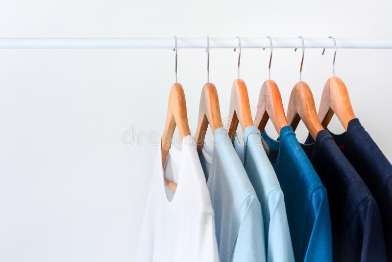 Samlingsskugga av blåa t-skjortor för signalfärg som hänger på träklädhängare i garderob royaltyfri bild