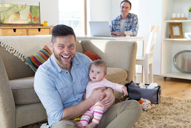 Samma könsbestämmer par hemma med dottern royaltyfria foton