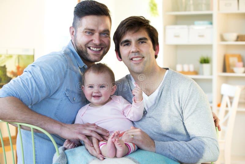 Samma könsbestämmer par med den hemmastadda dottern royaltyfri foto