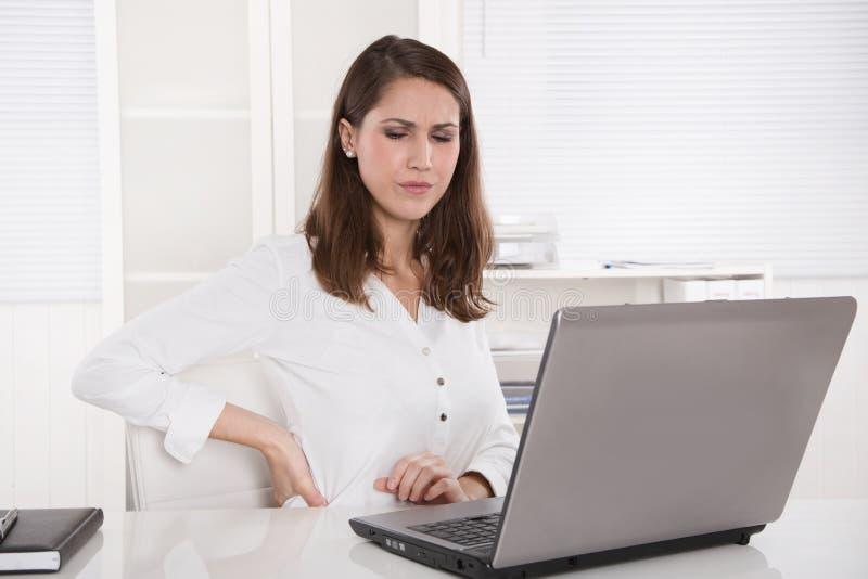 Sammanbrott: trött affärskvinna som rynkar pannan på bärbara datorn - tillbaka plågor eller royaltyfri fotografi