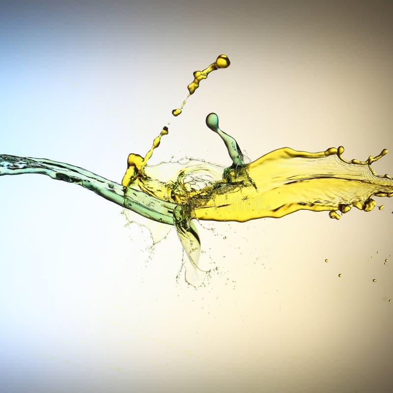 Sammandrabbning av guling- och blåttvätskestrålar fotografering för bildbyråer