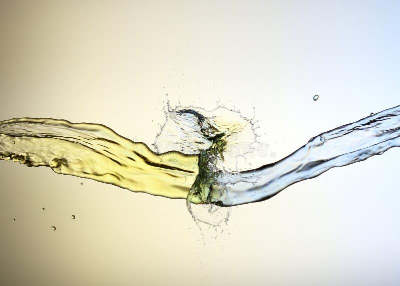 Sammandrabbning av guling- och blåttvätskestrålar arkivfoton