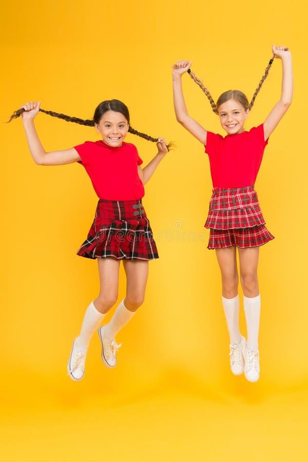 Sammanfoga ber?m Skolalikformig Skotsk stil Gladlynta vänskolflickor som hoppar gul bakgrund fira arkivbilder