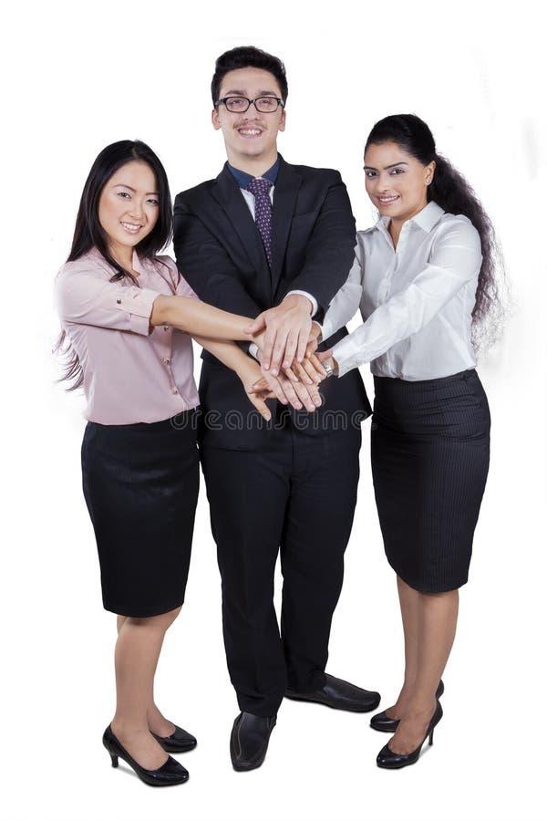 Sammanfogande händer för upphetsad teamwork i studio arkivbilder