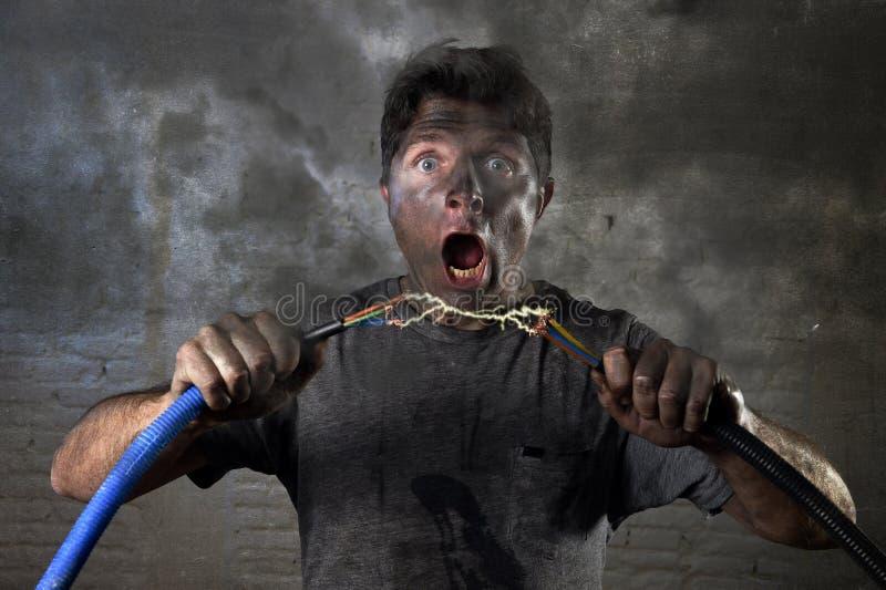Sammanfogande kabel för icke-utbildad man som lider elektrisk olycka med smutsigt bränt framsidachockuttryck royaltyfri fotografi