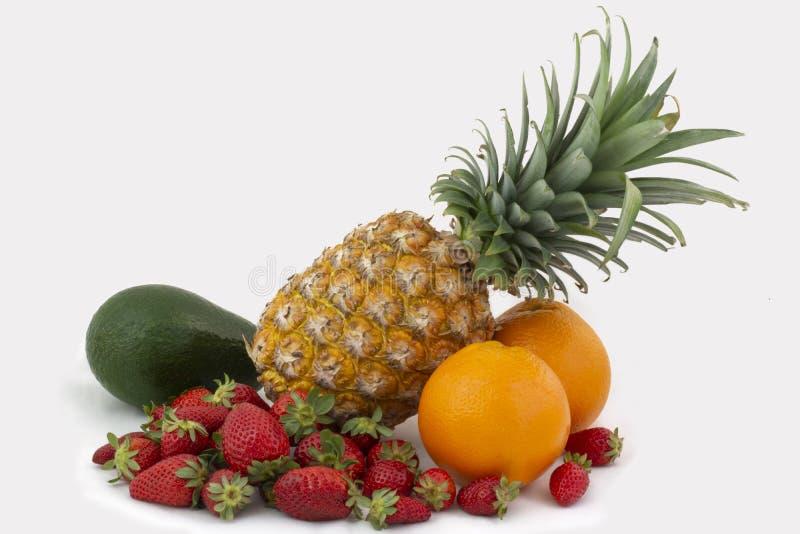 Sammansättning av ananas, jordgubbar, avokadot och apelsiner på en vit bakgrund royaltyfri bild