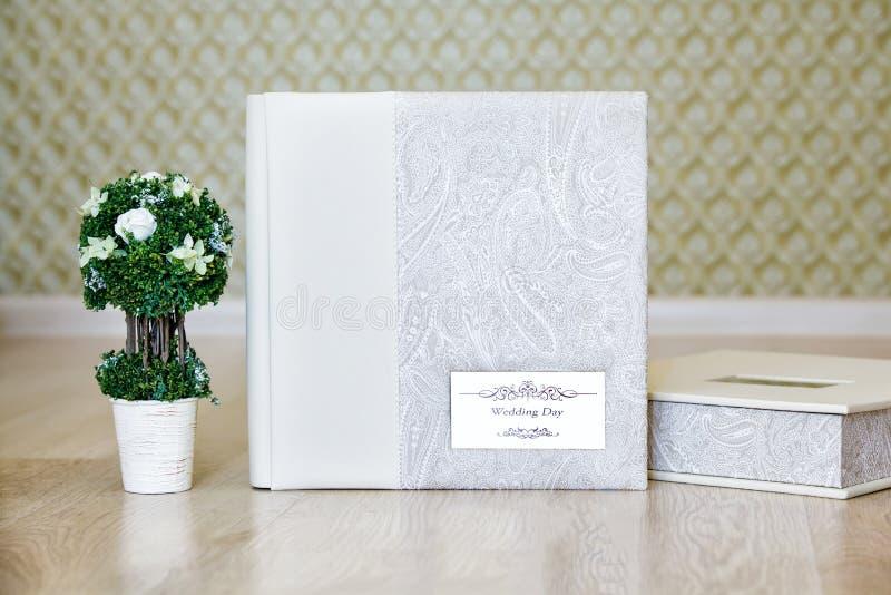 Sammansättning av bröllopfotoalbumet och det dekorativa trädet arkivbilder
