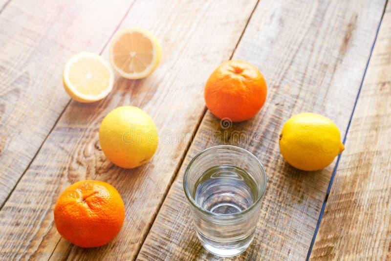 Sammansättning av citroner, apelsiner och exponeringsglas med vattenträtabellen royaltyfri foto