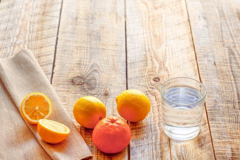 Sammansättning av citroner, apelsiner och exponeringsglas med vattenträtabellen royaltyfria bilder