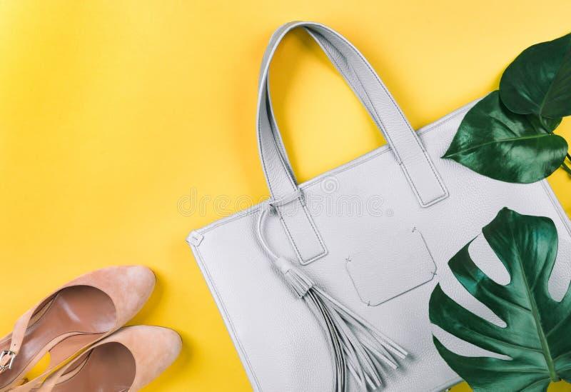 Sammansättning av den kvinnliga handväskan, skor och det gröna bladet arkivbild