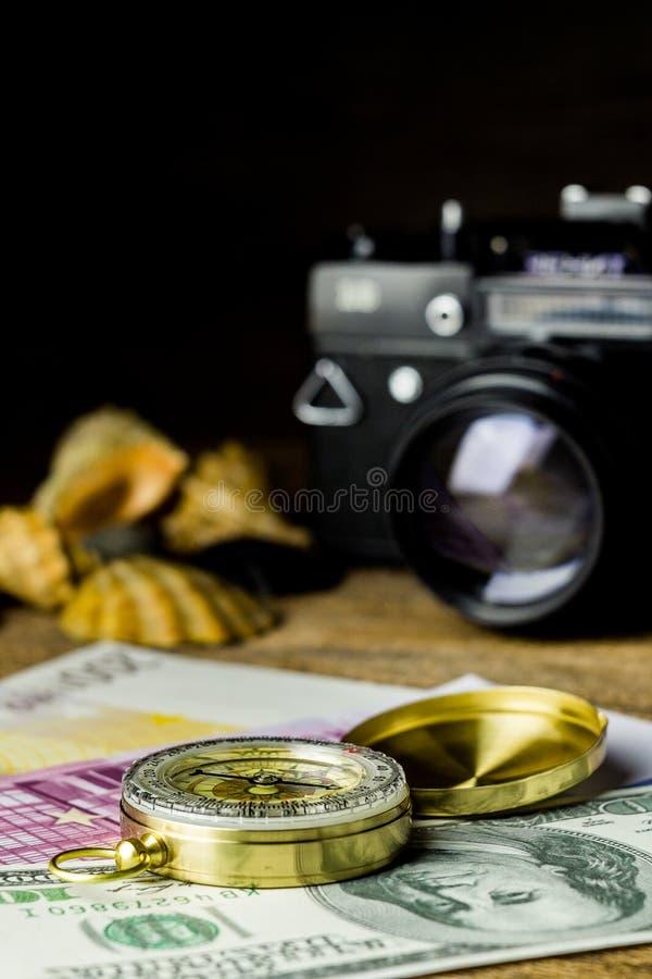 Sammansättning av den turist- kompasset, pengar, skal och fotocameraen på trätabellen royaltyfria foton