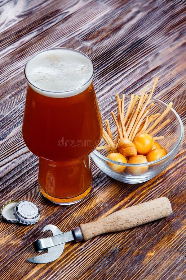 Sammansättning av ett exponeringsglas av öl med skum på en lantlig trätabell bredvid en bunke av salta mellanmål och en flasköppn royaltyfri fotografi