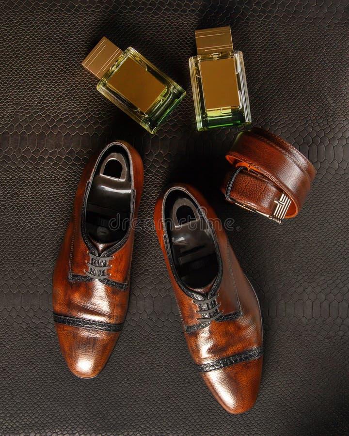 Sammansättning av ett par av mäns skor av brun färg, två flaskor av mäns doft och mäns byx- bälte mot bakgrunden royaltyfria foton
