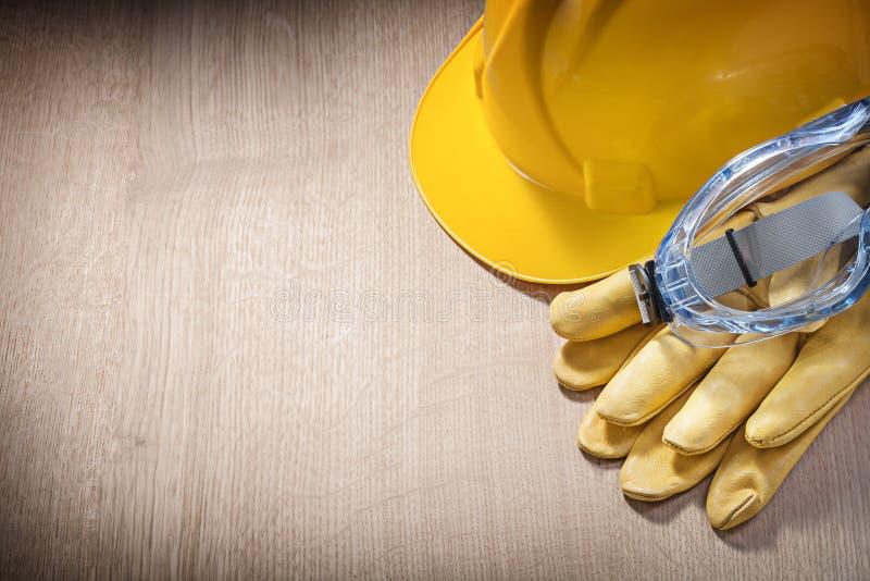Sammansättning av för säkerhetshandskar för hård hatt anblickar på träbräde arkivfoto