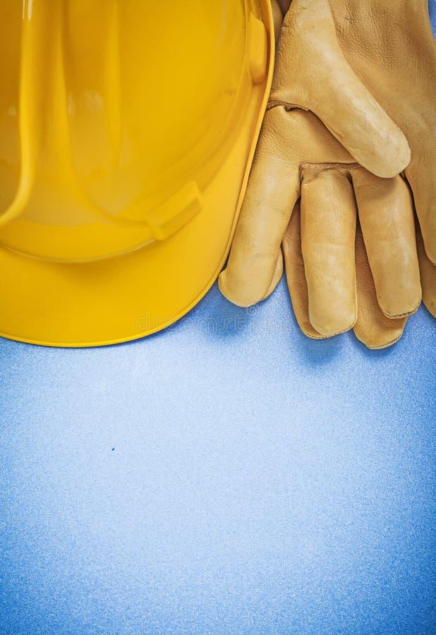 Sammansättning av gula skyddande handskar för hård hatt på blå backgro royaltyfria foton