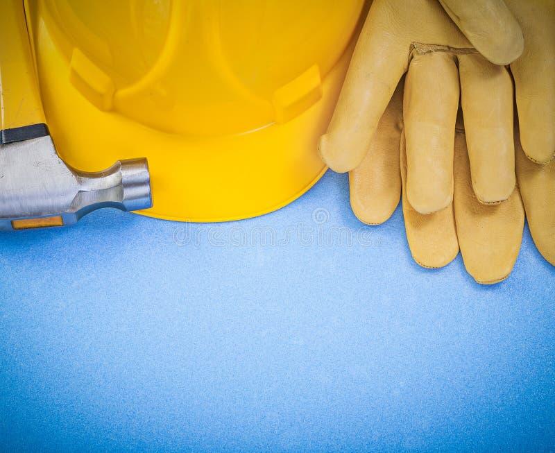 Sammansättning av handskar för säkerhet för jordluckrarehammare som bygger hjälmen på blått arkivbild