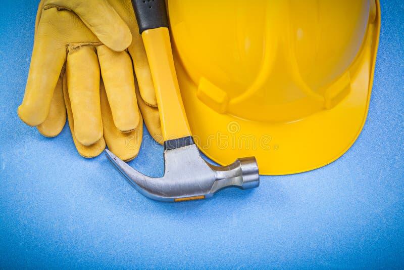 Sammansättning av hatten för handskar för säkerhet för jordluckrarehammare den hårda på blå backgr royaltyfria bilder