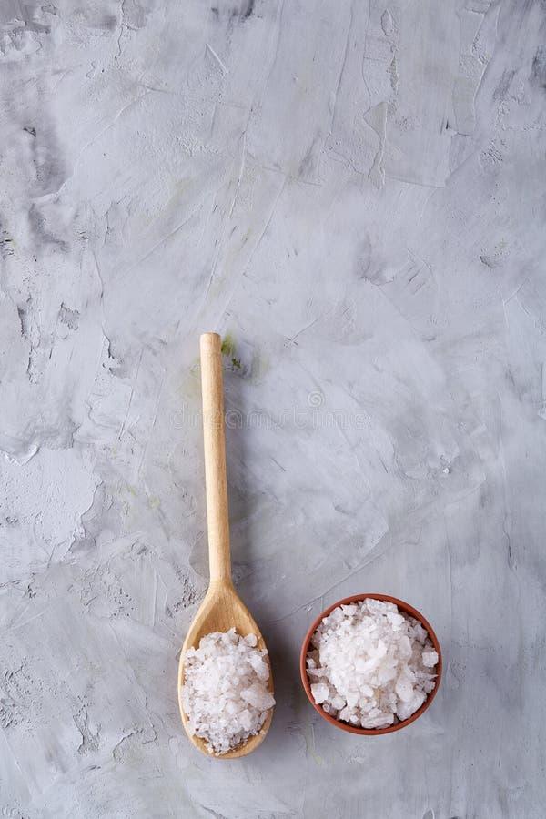 Sammansättning av havet som är salt i den keramiska bunke och skeden för att laga mat eller brunnsorten på vit bakgrund, bästa si arkivfoto