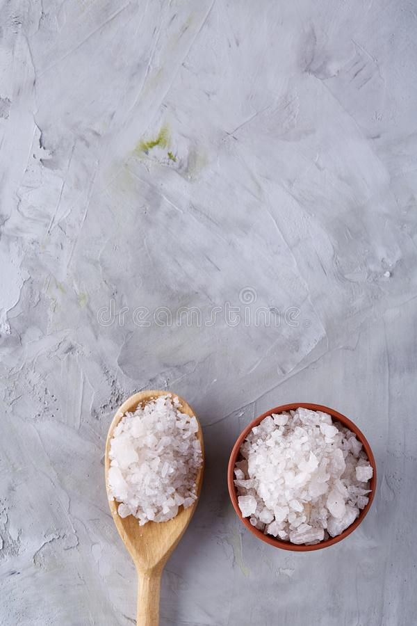 Sammansättning av havet som är salt i den keramiska bunke och skeden för att laga mat eller brunnsorten på vit bakgrund, bästa si fotografering för bildbyråer