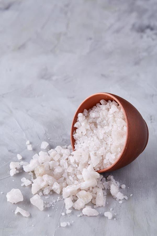 Sammansättning av havet som är salt i den keramiska bunke och skeden för att laga mat eller brunnsorten på vit bakgrund, bästa si arkivbild