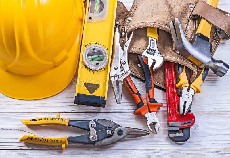 Sammansättning av hjälmen för bälte för hjälpmedel för byggnadsverktygsläder på träbräde arkivbilder