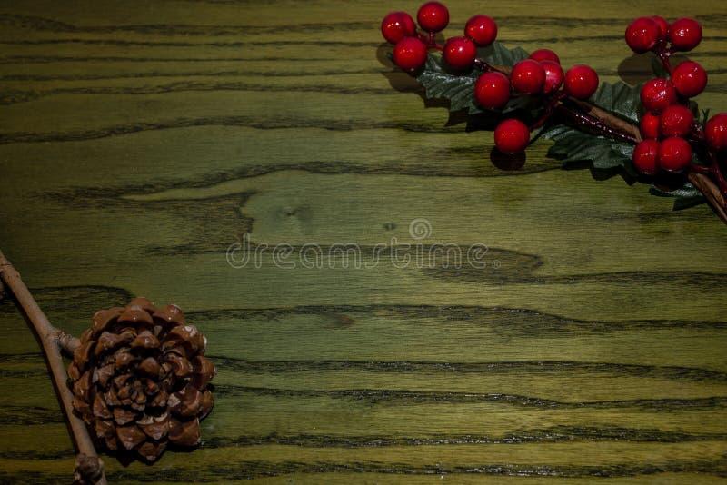 Sammansättning av julpineconen, filialer av järnekar på grön träbakgrund arkivbilder