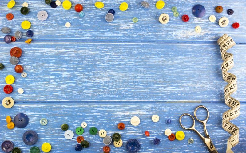 Sammansättning av knappar på en blå träbakgrund knäppas arkivfoton