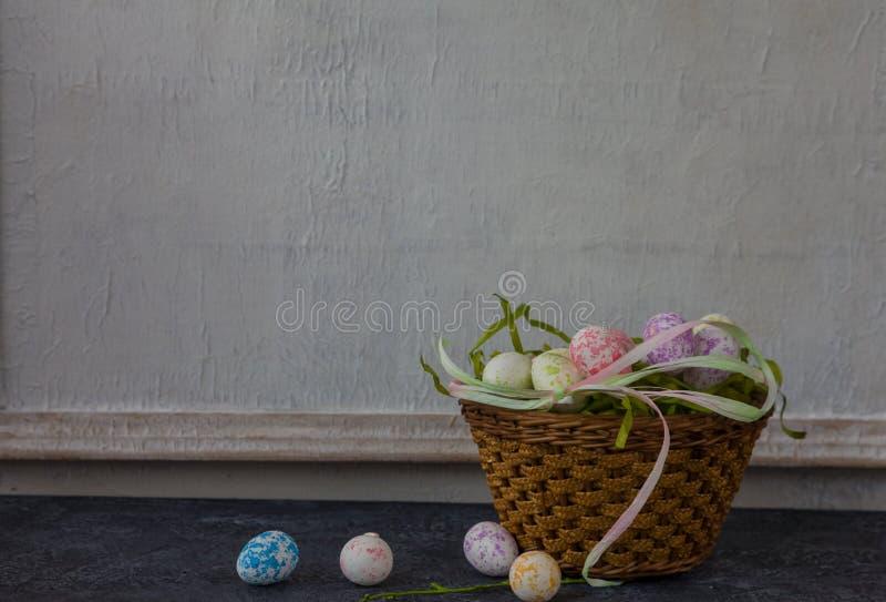 Sammansättning av målade påskägg på mörker stenar för tabellen och vit väggbakgrund för tappning royaltyfria foton