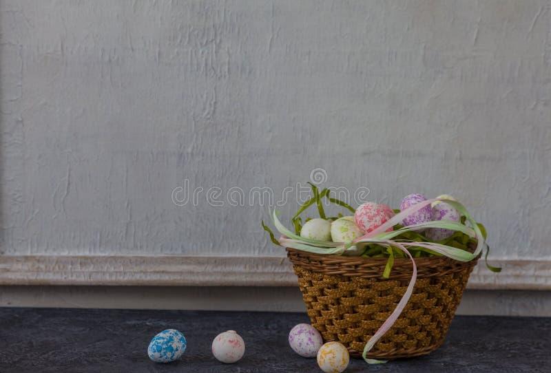 Sammansättning av målade påskägg på mörker stenar för tabellen och vit väggbakgrund för tappning royaltyfri foto