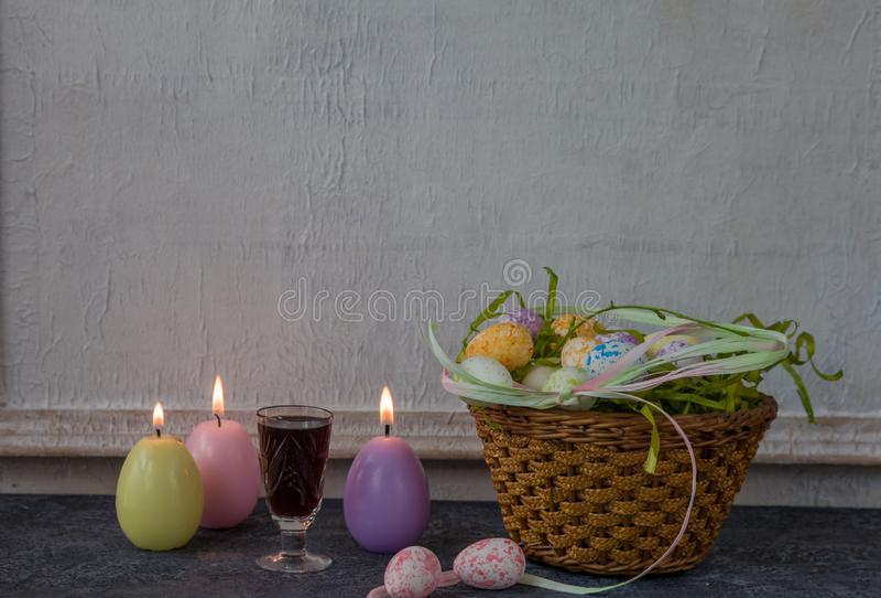 Sammansättning av målade påskägg på mörker stenar för tabellen och vit väggbakgrund för tappning arkivfoton