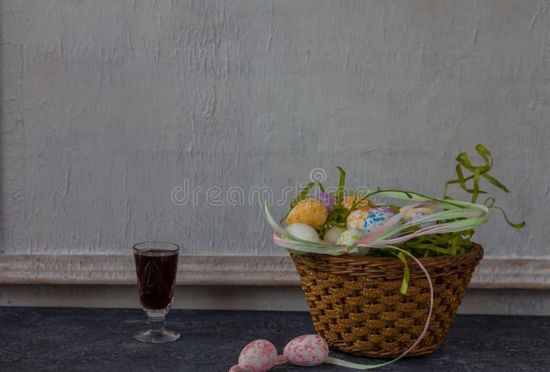 Sammansättning av målade påskägg på mörker stenar för tabellen och vit väggbakgrund för tappning royaltyfri bild
