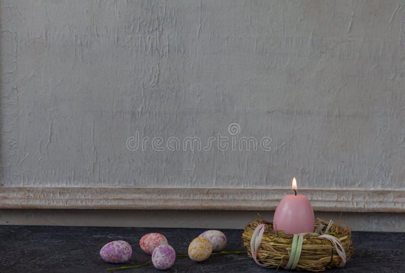Sammansättning av målade påskägg på mörker stenar för tabellen och vit väggbakgrund för tappning fotografering för bildbyråer