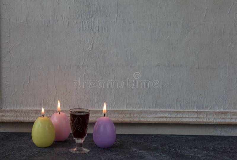 Sammansättning av målade påskägg på mörker stenar för tabellen och vit väggbakgrund för tappning arkivbild