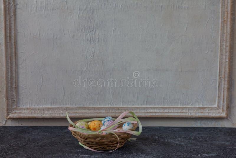 Sammansättning av målade påskägg på mörker stenar för tabellen och vit väggbakgrund för tappning royaltyfria bilder